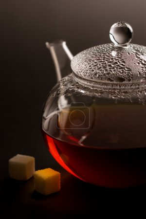 Teapot with black tea and sugar