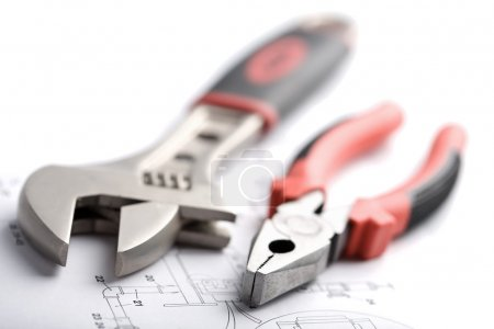 Wrench and pliers over technical drawing isolated...