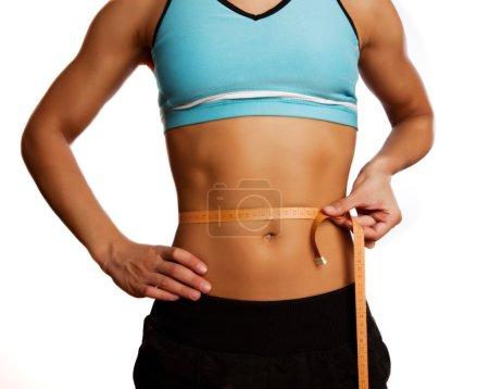 Foto de Bonito atleta mide vientre con regla - Imagen libre de derechos