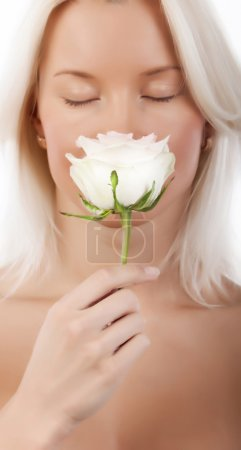 Sexy blonde smelling a rose