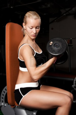 Beautiful athlete lifting heavy weights