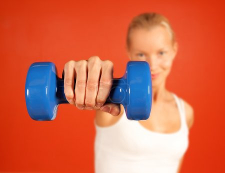 Young attractive woman lifting weights