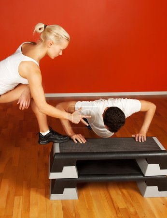 Trainer and trainee in fitness room