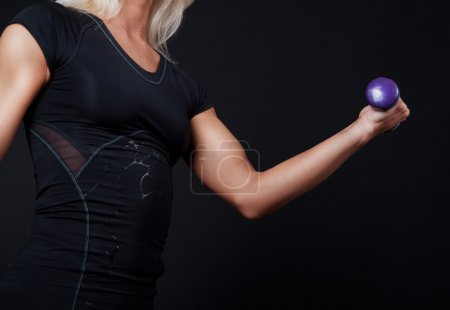 Photo for Violet dumbbell in girls hands - Royalty Free Image