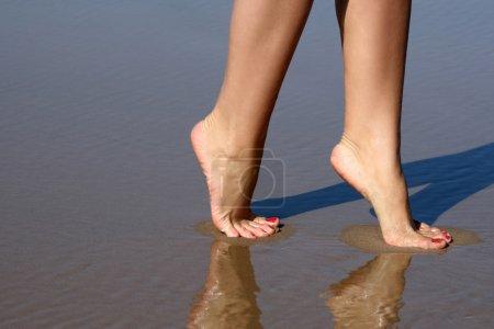 Photo pour Jolies jambes d'une jolie fille marchant dans l'eau - image libre de droit