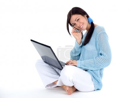Photo for Brunette talking at a cellphone and working at laptop - Royalty Free Image