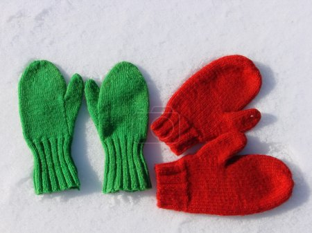 Photo for Two pairs hand knit mittens on snow - Royalty Free Image