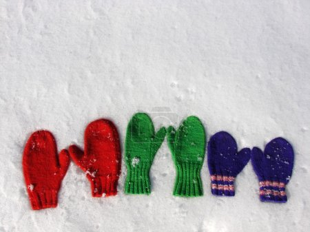 Photo for Three pairs hand knit mittens on snow - Royalty Free Image