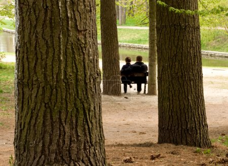 The loving couple sits on a bench in spring park...