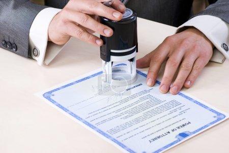 Photo pour Gros plan des mains masculines du notaire sur la procuration. Document et signature du fictif - image libre de droit