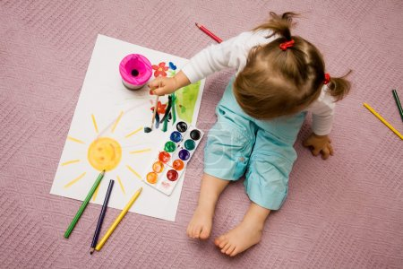 Photo for The small beautiful girl paints on a paper - Royalty Free Image