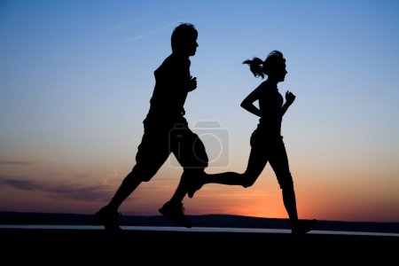Photo for The man and the woman run together on a sunset on lake coast - Royalty Free Image