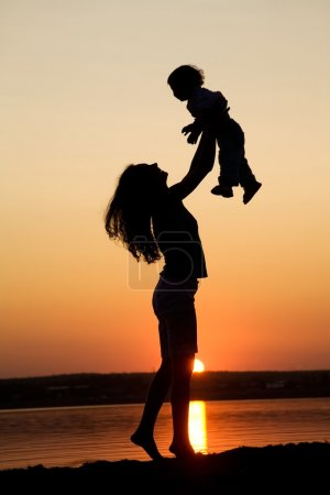 Photo for Silhouette of mother which turns the child against a sunset and water - Royalty Free Image