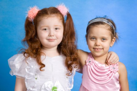 Photo for Two smiling little girls isolated on blue background - Royalty Free Image