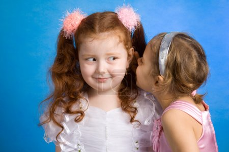 Two little girls talking in whispers