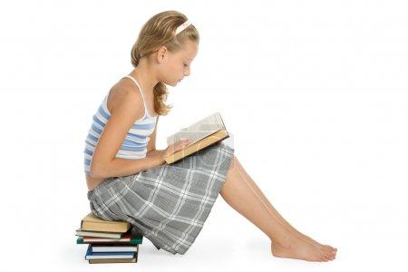 Photo pour Jolie adolescente assise sur le sol et lisant le livre - image libre de droit