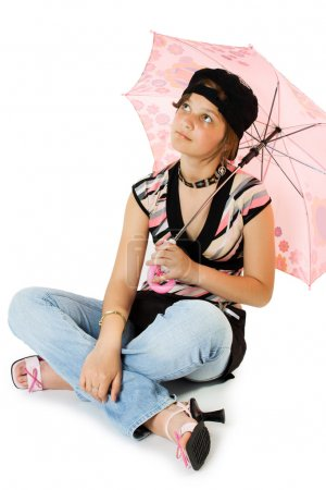 Young girl with umbrella sits on floor