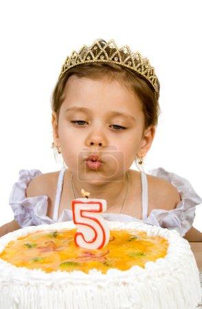 Photo pour Une petite fille soufflant les bougies sur son gâteau d'anniversaire. Gâteau d'anniversaire célébrant cinq ans . - image libre de droit