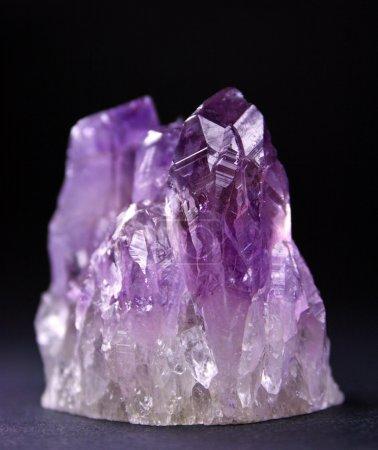 Crystals of magenta amethyst shined on a dark back...