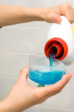 Photo for Pouring washing gel in plastic measuring container - Royalty Free Image