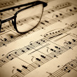 A closeup of a sheet of piano music and goggles...