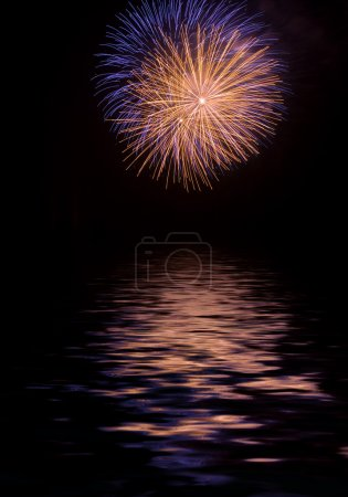 Exploding fireworks with reflexes on water at nigh...