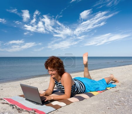 Girl with laptop at sea shore