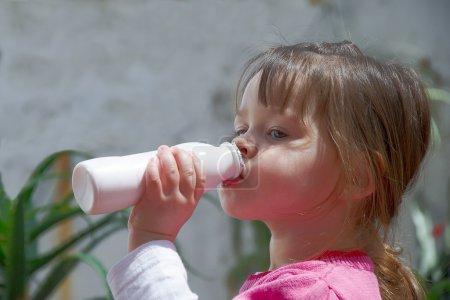 Little girl drinking yogurt