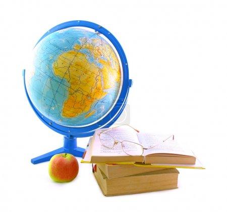 Photo pour Le globe, trois livres, pomme mûre et lunettes. Il est isolé sur fond blanc. - image libre de droit