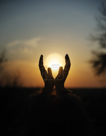 Photo for Decline in hands. A sunset on a background of the lifted female hands - Royalty Free Image