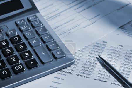 Photo pour La calculatrice et le rapport financier. Un lieu de travail de l'homme d'affaires. Contraste élevé - image libre de droit