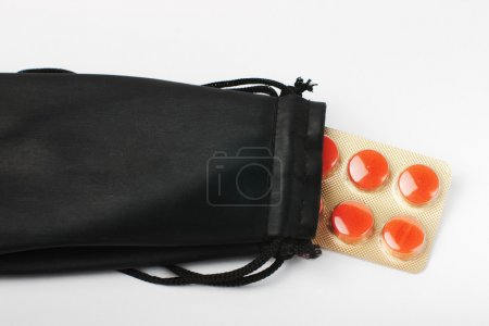 Red pills inside black pouch
