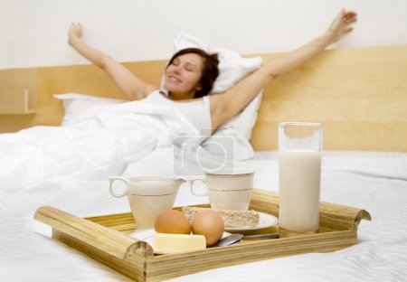 Photo for Young woman has a breakfast in the bed - Royalty Free Image