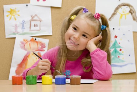 Photo for Little girl paints pictures in bright colours - Royalty Free Image
