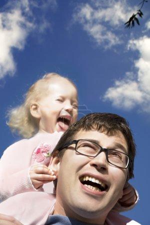 Photo pour Petite fille assise sur les épaules de son père - image libre de droit