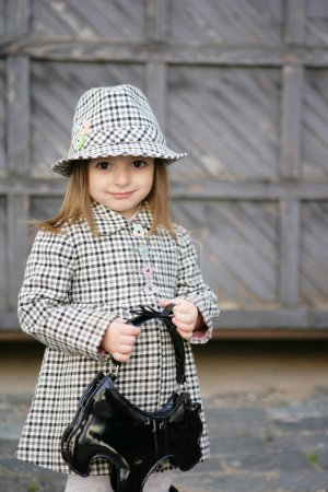 Photo for A small woman of fashion in a checked coat and hat. In the hands of black handbag - Royalty Free Image