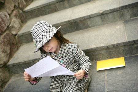 Photo for Romantic little girl sitting on the stairs with a romantic letter - Royalty Free Image