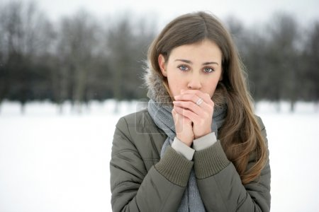 Photo for Girl in the park in winter warms the hands of breath - Royalty Free Image