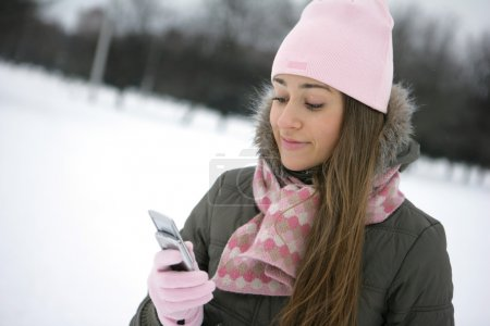 Photo for Beautiful young woman reading sms on her cellular phone - Royalty Free Image