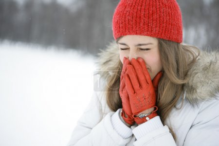 Photo for Young brunette in a park in winter sneezes. Closes mouth with her hands - Royalty Free Image