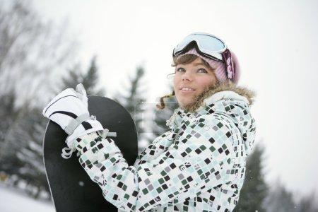 Photo pour Une fille dans une combinaison de ski dans les montagnes en hiver près de snowboard noir - image libre de droit