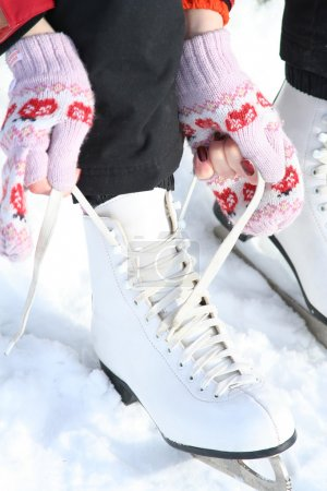Photo for Girl in dress skates mittens tying shoelaces and prepare for skating - Royalty Free Image