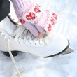 Girl in dress skates mittens tying shoelaces and p...
