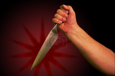 Photo for A hand holds a knife ready to stab. With clipping path so you can easily remove from background, - Royalty Free Image