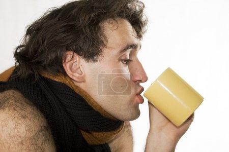 Flu. Influenzal man drinks hot tea