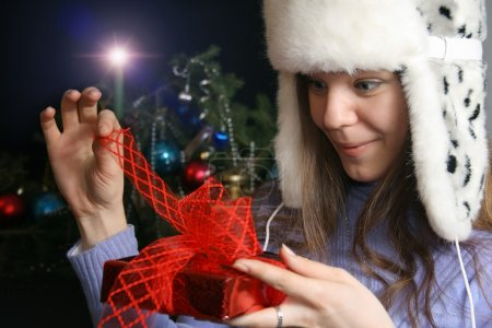 Young Woman Unwrapping Christmas Gift