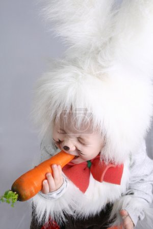 Photo for Child in a white downy bunny costume and holds the carrot. - Royalty Free Image