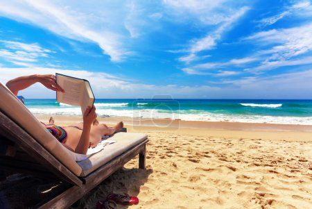 Photo for Girl reading book and relaxing on the beach - Royalty Free Image