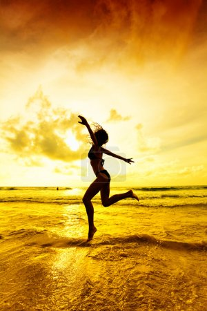 Photo for The jumping girl on a tropical beach - Royalty Free Image