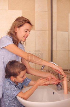 Photo pour Maman avec le fils se laver les mains - image libre de droit